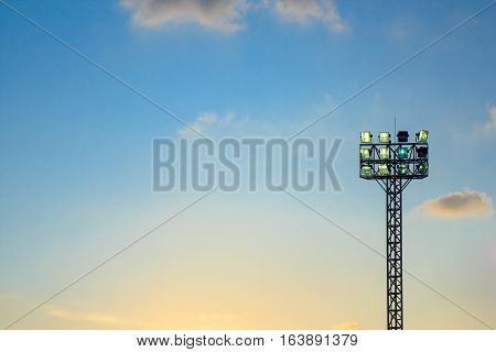 Lighting tower of stadium on sky and cloud background.