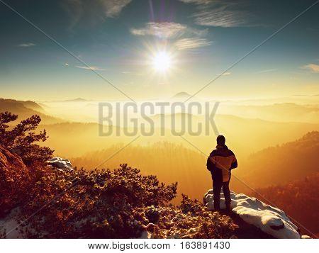 Tall hiker in black on rocky peak watch the world . Heavy orange mist bellow in valley. Wonderful breathtaking daybreak in mountains.