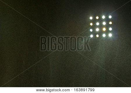 Spotlight of football stadium with rain at night.