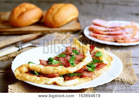 Ruddy bacon omelet. Fried omelet stuffed with bacon and parsley on a plate. Bacon slices on a plate, knife, fork, buns on old wooden table. Egg breakfast idea. Closeup