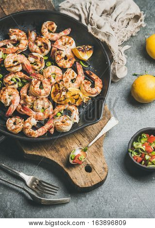 Seafood dinner. Grilled tiger prawns in cast iron grilling pan with fresh lemon, leek, chili pepper and mint salsa sauce over grey concrete background, top view. Slow food concept