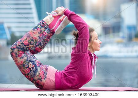 Young attractive woman practicing yoga, stretching in Bow exercise, Dhanurasana pose, working out wearing pink sportswear, outdoor full length, modern skyscraper and river background