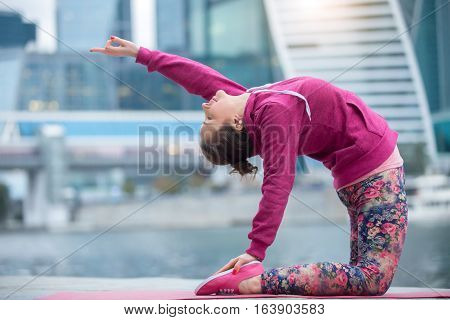 Young attractive woman practicing yoga, sitting in Camel exercise, Ustrasana pose, working out wearing pink sportswear, outdoor full length, modern city and river background
