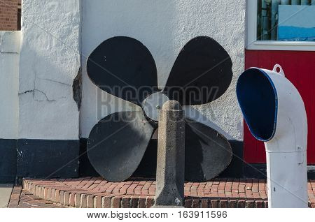 Ship equipment in front of a building wall. Large ship's screw and ventilation shaft.