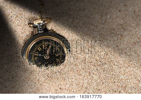 Detail of an old and small pocket watch partially buried in the sand