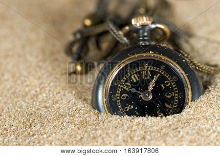 Old and small pocket watch with chain partially buried in the sand