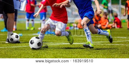 Boys Soccer Football Game. Football Soccer Match for Children. Kids Playing Soccer Game Tournament. Boys Running and Kicking Football. Youth Soccer Coach in the Background