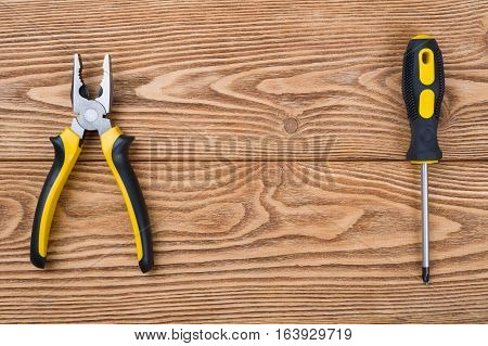 Pliers and screwdriver on a wooden background