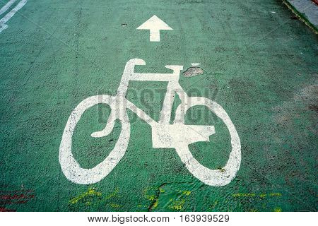 Bicycle lane sign white bicycle on green pavement background