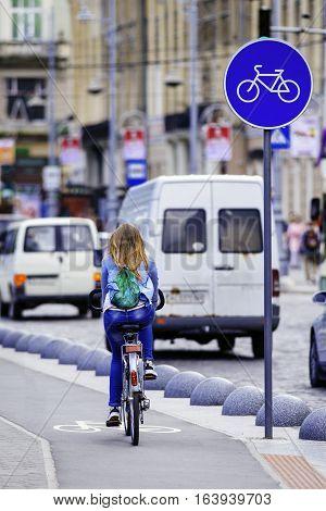 Young woman ride bicycle on bicycle lane. Bicycle lane sign. Bicycle. Pedestrian.