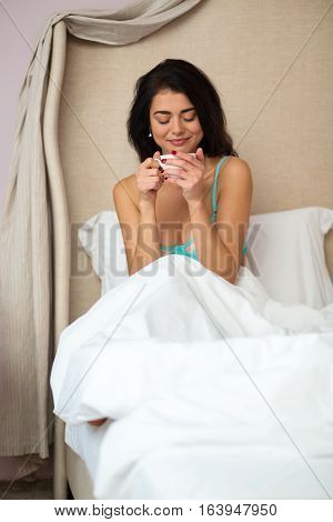 Woman holding cup in bed. Smiling girl with closed eyes. Refined taste of coffee.