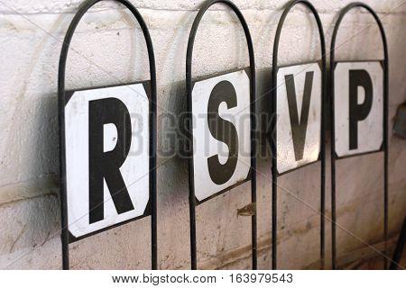 signpost with letters spelling rsvp respondez s'il vous plait