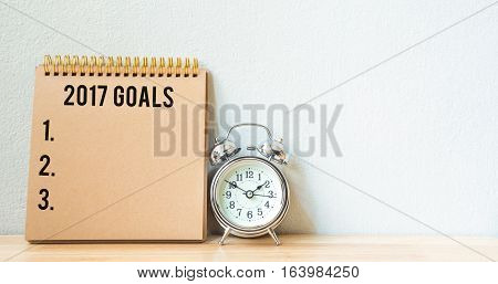 2017 goals list with notebook and alarm clock on wood table