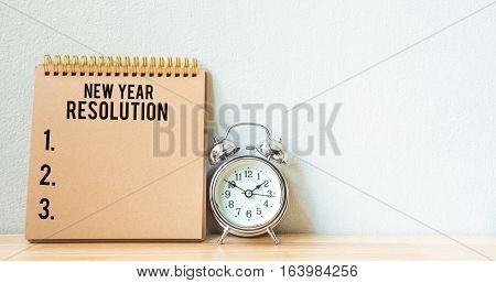 New Year's Resolution on a notepad and alarm clock on wood table