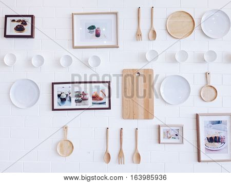Kitchenware and photo frame hanging on white brick wall, vintage style