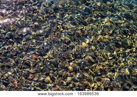 Colorful rocks on the bottom of Lake Crescent in Washington state show clearly through the crystal clear water