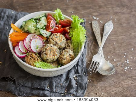 Quinoa meatballs and vegetable salad. Buddha bowl on a wooden table top view. Healthy diet vegetarian food concept. Flat lay