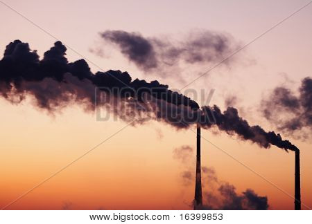 Air polluting smokestack against sunset sky