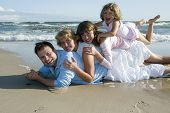 picture of family fun  - Happy family playing together on the beach - JPG
