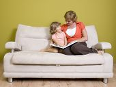 foto of mother daughter  - Mother and daughter reading book on sofa - JPG