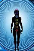 female silhouette figure and chakras symbols against spiral background