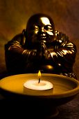 statue of happy Buddha with candle light in gold tonality