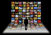 man standing in front of flat panels screens with images, concept for digital television