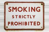 Rusted old sign with text 'Smoking strictly prohibited'