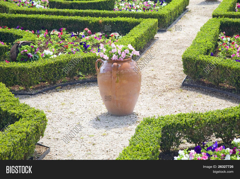 de barro grande y setos de boj recortados son parte de los jardines