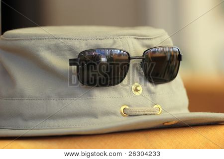 hat and sunglasses on a table with reflection of cafe in the lens
