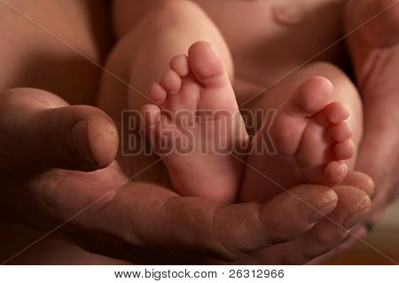 Daddy's hand holding baby's feet