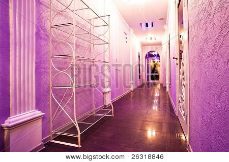 Long purple corridor in barbershop interior with mirrors