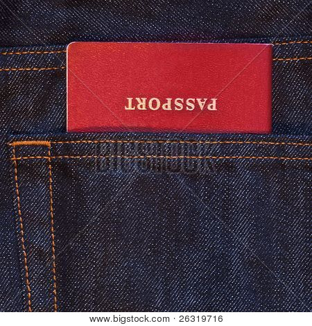 Dark blue jeans pocket with red passport in it