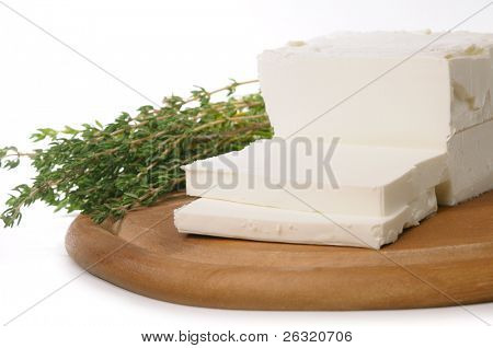 goat's milk cheese in block, sliced with thyme on white