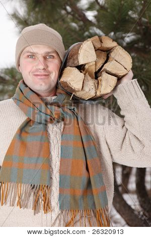 man with firewood in winter day
