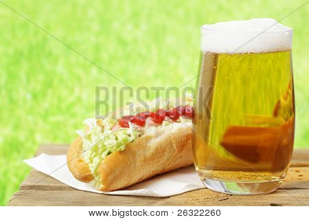 Hot dog with catchup and a glass of beer