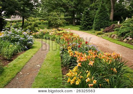 A lane running through a park and alongside flower beds.