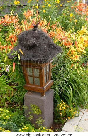 A Thai themed garden lantern framed with daylilies.