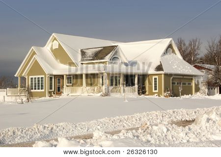 A contemporary home covered with freshly fallen snow.