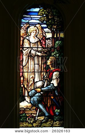 Stained glass window of an angel presenting a head garland of leaves to a young soldier, possibly Joan of Arc.