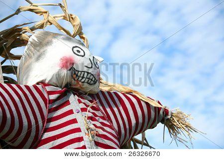 eine Stroh gefüllt Halloween Vogelscheuche silhouetted gegen eine fleckige blau Himmel.