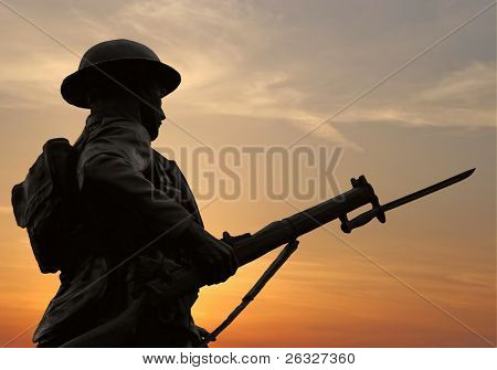 The silhouette of a WW1 soldier figure in a war monument against a sunset sky.