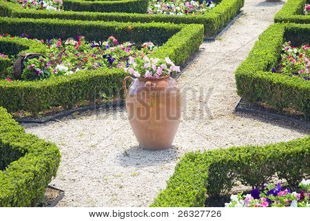 Large clay planters and clipped boxwood hedges are part of the formal gardens in the Bermuda Botanical Gardens.  Petunias fill in the spaces amongst the hedges.