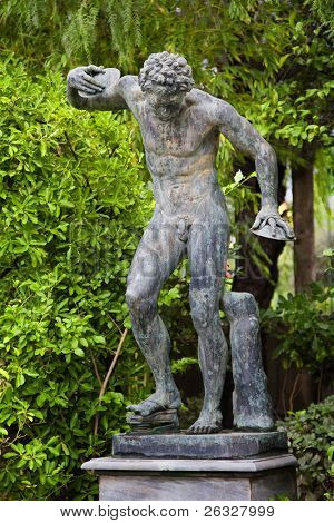 A replica of an ancient greek statue showing a disk thrower athlete in the gardens of the Achillion Palace on the Greek island of Corfu.