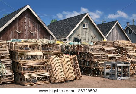 Bait sheds on a wharf in Prince Edward Island, Canada. Lobster traps and buoys are stacked in front. Tails of a tunas hang  on the shed walls.