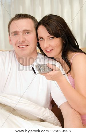 Couple watching TV from their bed