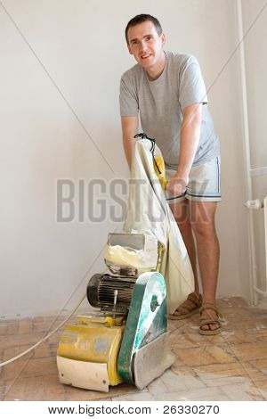 Cheerful man sanding (scraping) floor