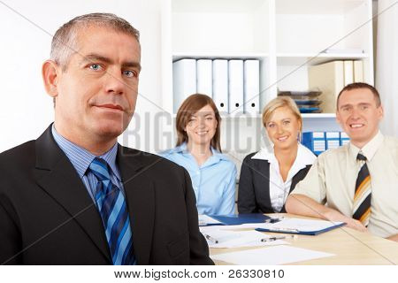 Business group at the meeting, mature man in front