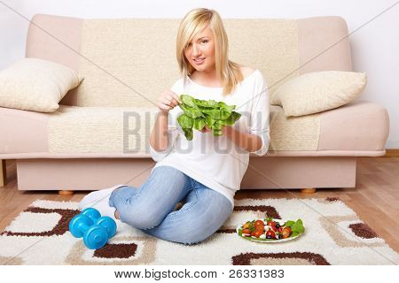 Beautiful woman with head of lettuce and dumb-bell, healthy food concept