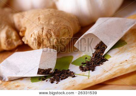 Tea scattered over illustration of herbs, ginger in the background